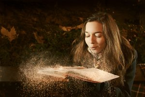 Girl blows snow from opened book in the winter park