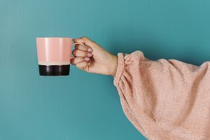 Closeup of hand holding coffee cup
