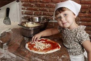 Little girl adding cheese to pizza.