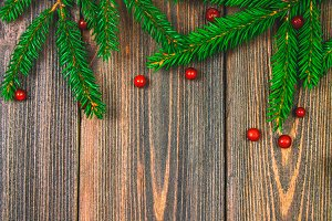 Spruce branches with red berries on a wooden table. copy space.