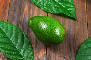 One green ripe raw avocado fruit with leaves lies on a wooden brown table. Top view.