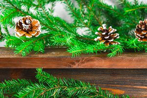 Red New Year's cones lie on a wooden brown shelf surrounded by fir branches.
