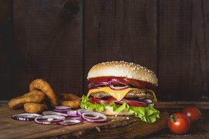 Cheeseburger and onion rings on wooden cutting board over wooden background.