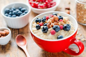 Oatmeal porridge bowl with blueberries, nuts and raspberries
