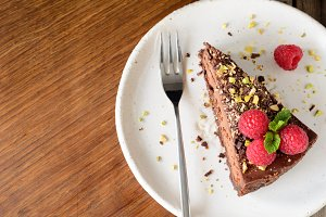 Slice of chocolate cake topped with raspberries, pistachio nut and mint leaf on white plate.
