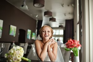 Bride smiles broad while sitting