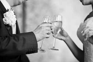 Newlyweds hands clanging champagne
