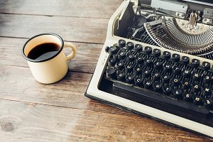 Morning writer. An old printing machine and a mug of hot coffee stand on a wooden table