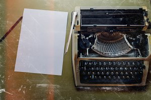 A vintage typewriter, a white sheet of paper and a black pencil lie on a green surface, a top view