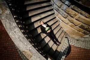 Young groom lying on the stairs