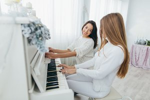 Girls play the piano on Christmas