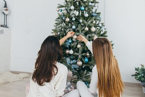 Girls decorating a christmas tree.