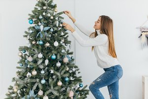 Girl is decorating a christmas tree.