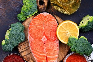 Steak of raw salmon with lemon and olive oil on a dark background Top view.