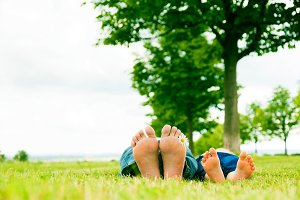 Little Girl's And Father's Feet With Daisy Flowers