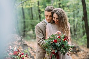 Groom tenderly embrace his beautiful bride by behind. Autumn wedding outdoors. Happy newlyweds