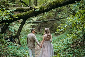 A happy couple is walking on a trail in an autumn forest. Bride and groom are looking at each other on nature.