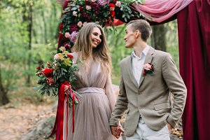 Stylish bride and groom with are holding hands next to wedding arch. Autumn wedding ceremony in forest. Happy newlyweds
