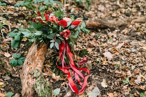 Beautiful wedding bouquet of different flowers lying on a log in the park. Autumn wedding
