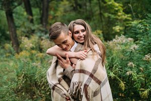 Beautiful girl is tenderly embracing her boyfriend by the plaid by behind. Happy newlyweds