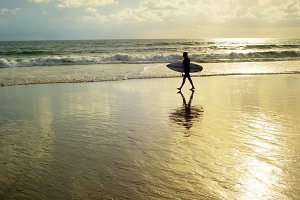 Surfer walking at the beach