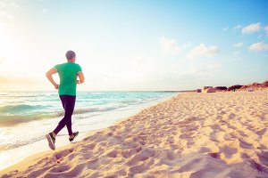 Young Man Jogging On The Beach
