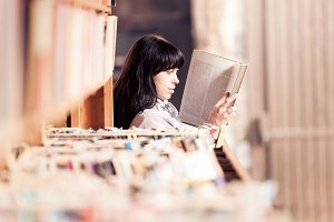 Young Woman Looking At Books In A Bookstore