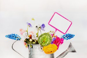 Watering can with flowers and sign