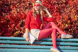 Fall Fashion. Young Woman Sitting on Bench
