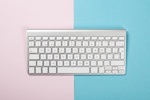 Computer keyboard on pink and blue background. Technology