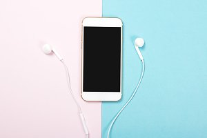 Smartphone and headphones on pink and blue background. Technology
