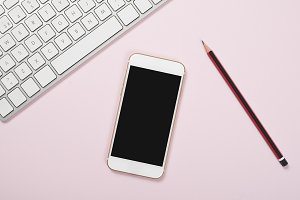 Smartphone next to computer keyboard and pen on pink background. Technology