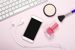Smartphone, headphones and computer keyboard next to makeup and paints nails on pink and blue background. Technology