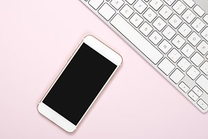 Smartphone and computer keyboard on pink and blue background. Technology
