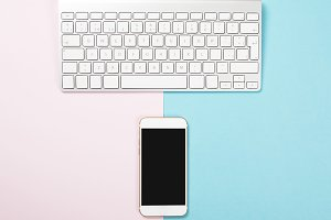 Computer keyboard and smartphone on pink and blue background. Technology