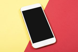 Smartphone on red and yellow background. Technology