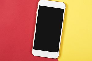 Top view of smartphone on red and yellow background. Technology
