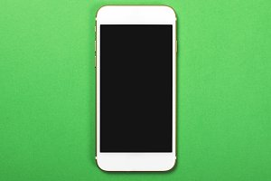 Top view of smartphone on green background. Technology