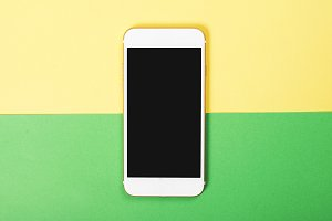 Top view of smartphone on yellow and green background. Technology