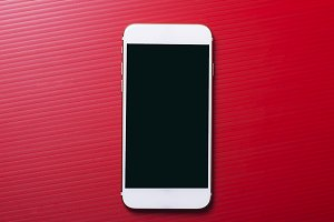 Top view of smartphone on red background. Technology