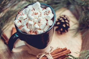 New Year and Christmas concept. Hot chocolate with marshmallow in a clay black and white mug on an old wooden board decorated with spruce branches and cinnamon sticks. Top view.