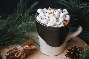 New Year and Christmas concept. Hot chocolate with marshmallow in a clay black and white mug on an old wooden board decorated with spruce branches and cinnamon sticks.