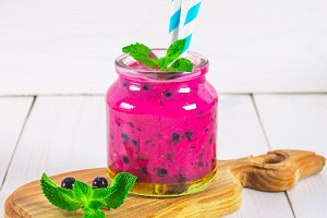 Smoothies of black currant in a glass jar with straws on a white wooden table.