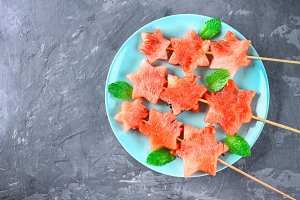 Watermelon in the form of stars on skewers with leaves of mint lies on a plate. The blue dish is like a rocket in space. Top view.