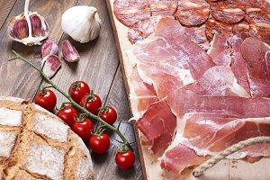 Top view of plate with ham, chorizo and loin embuchado next to bread, tomatoes, garlic and oil on wooden background. Spanish typical food