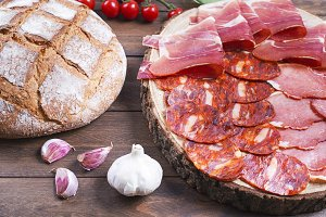 Top view of plate with ham, chorizo and loin sausage next to bread, tomatoes and garlic on wooden background. Spanish typical food