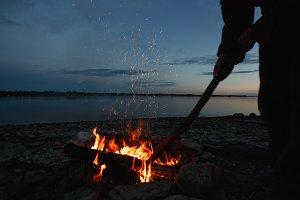Traveler making bonfire at night