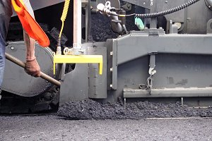 Road construction. Workers applying new asphalt.