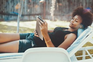 Black girl with tablet pc in park