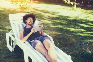 Afro girl on lounge chair with pad